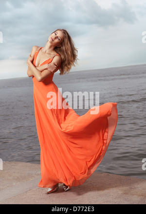 Belle jeune femme en robe d'été orange au vent debout sur une mer Banque D'Images