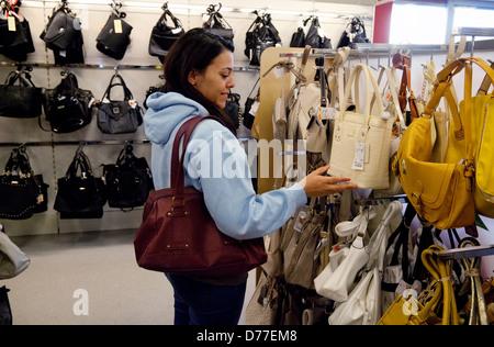 Une adolescente shopping pour acheter un sac à main dans un magasin T.K.Maxx, Newmarket, UK Banque D'Images