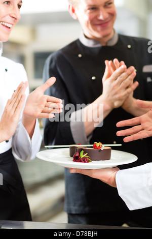 L'équipe de chef de cuisine du restaurant avec dessert, les collègues applaudir parce que l'antenne fonctionne très Banque D'Images