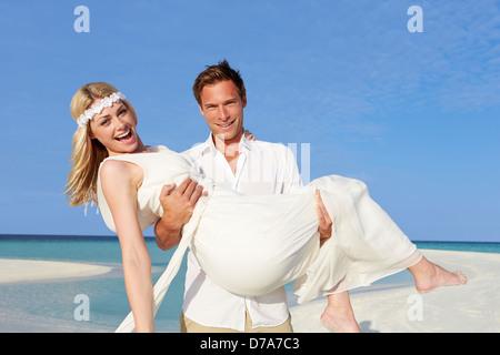 Groom exerçant son épouse au mariage de plage magnifique Banque D'Images