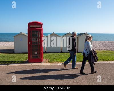 Vieux téléphone rouge fort et cabines de plage sur le front de Budleigh Salterton, Budleigh Salterton, Devon, Angleterre.