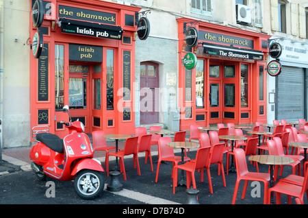 Vide ou Desrted pavé café au pub ou bar irlandais avec tables et chaises rouges et Scooter rouge Marseille Provence Banque D'Images