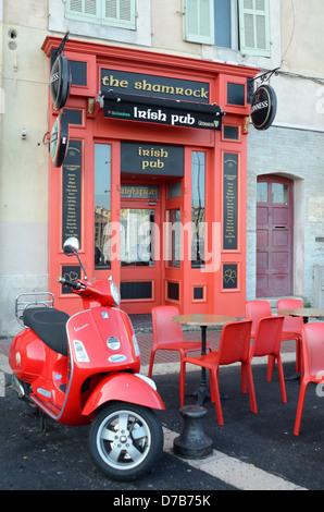 Pub irlandais fermé le Samrock & pavé déserté café ou bar avec tables et chaises en plastique Scooter rouge Vieux Banque D'Images