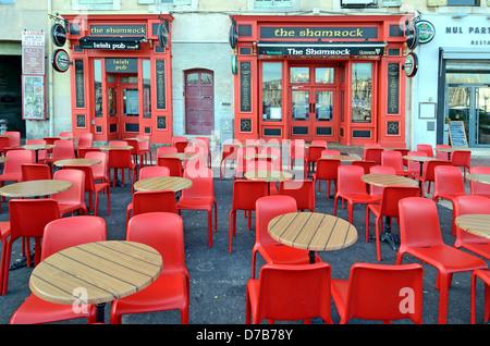 Bar-pub irlandais fermé ou café pavé vide avec tables désertes et chaises rouges en plastique Vieux-Port ou Vieux Banque D'Images