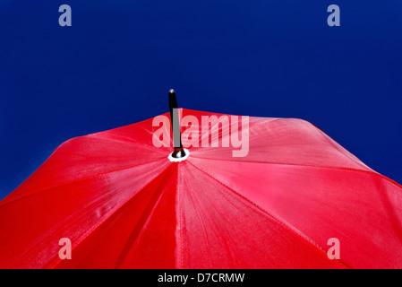 Taille grand parapluie rouge isolé en sombre ciel bleu clair. Banque D'Images
