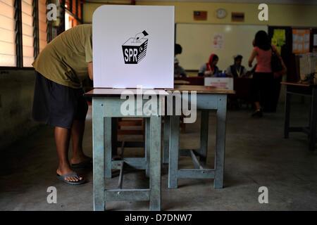 Kuala Lumpur, Malaisie. 5 mai, 2013. Un électeur de Malaisie marque son bulletin de vote à un bureau de scrutin Banque D'Images