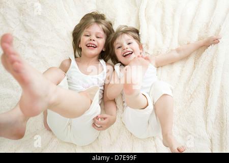 Happy little girls lying on retour vue d'en haut Banque D'Images