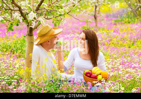 Young happy family having fun au printemps fleurs de jardin, cute Woman feeding her boyfriend apple, le romantisme Banque D'Images