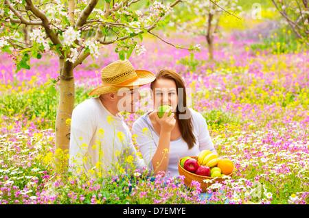 Young happy family having picnic sur champ de fleurs au printemps, le jardin de manger sain Aliments biologiques, Banque D'Images