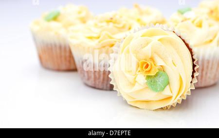 Cup cakes maison de luxe crémeux avec fleur détaillé et scintille Banque D'Images
