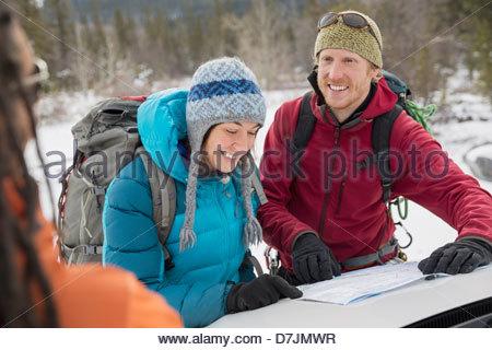 Groupe d'amis à la recherche de la carte dans les montagnes Banque D'Images
