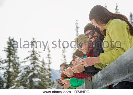 Groupe d'amis à l'aide de leur téléphone mobile dans les montagnes Banque D'Images
