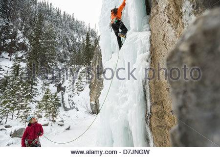 L'homme ami de l'assurage sur mur de glace dans les montagnes Banque D'Images