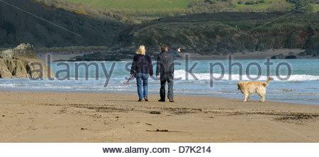 Un homme et femme marche un chien dans Bigbury-On-mer plage Bantham avec en arrière-plan. Banque D'Images