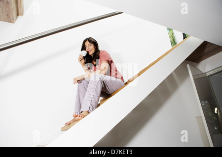 Allemagne, Berlin, young woman sitting on stairs, smiling Banque D'Images