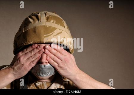 Soldat avec mains couvrant ses yeux et sa bouche bâillonnée par bande. Soldat est le port de l'uniforme militaire Banque D'Images