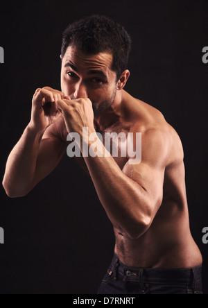 Jeune homme musclé sur fond noir avec les poings soulevées Banque D'Images