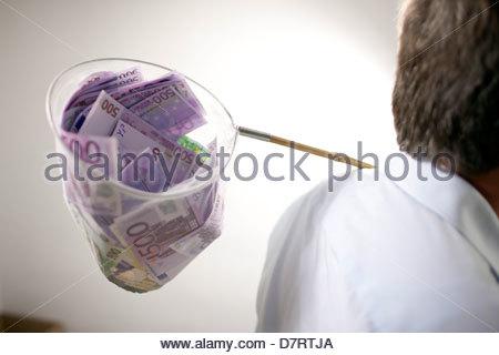 Portrait d'un homme tenant un filet de pêche rempli de 500 euro notes Banque D'Images