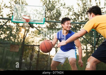 Deux joueurs de basket-ball de rue sur la cour de basket-ball Banque D'Images