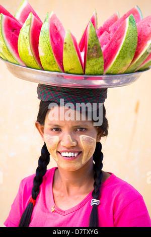Femme avec Thanakha visage traditionnel peinture, transportant un bac de melon sur sa tête, Shwezigon Paya, Birmanie, Banque D'Images