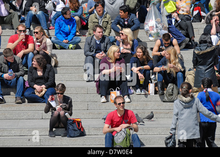 Londres, Angleterre, Royaume-Uni. Les gens assis sur les marches à Trafalgar Square Banque D'Images