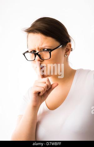 Une jeune brunette young woman wearing glasses avec son doigt sur ses lèvres, demandant le silence Banque D'Images