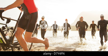 Triathletes emerging from water Banque D'Images