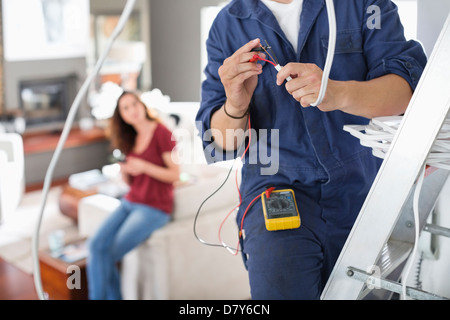 Electrician working in living room Banque D'Images