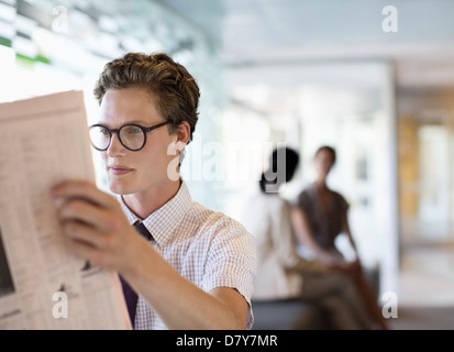 Businessman reading newspaper in office Banque D'Images