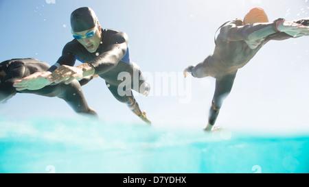 Les triathlètes en combis running into ocean Banque D'Images