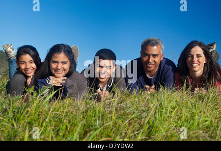 Hispanic family smiling in grass Banque D'Images