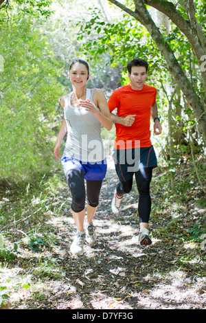 Couple running on dirt path Banque D'Images