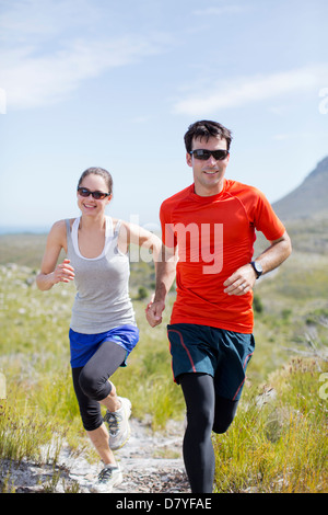 Couple running in rural landscape Banque D'Images