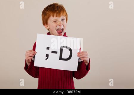 Caucasian boy holding carte avec smiley face