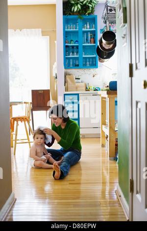 Mère hispanique avec tout-petit sur plancher de la cuisine Banque D'Images