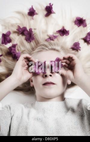 Belle fille blonde avec des fleurs dans ses cheveux et devant ses yeux Banque D'Images