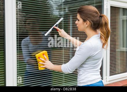 Jeune femme d'une fenêtre de nettoyage Banque D'Images