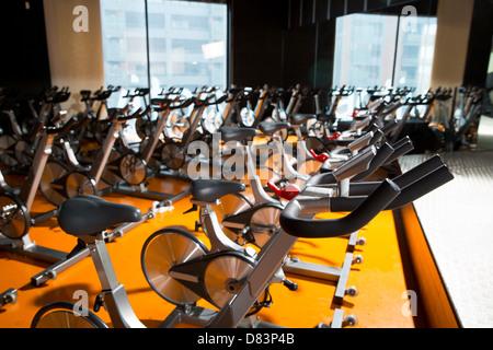 Spinning aérobic vélos d'une salle de gymnastique avec de nombreux d'affilée Banque D'Images