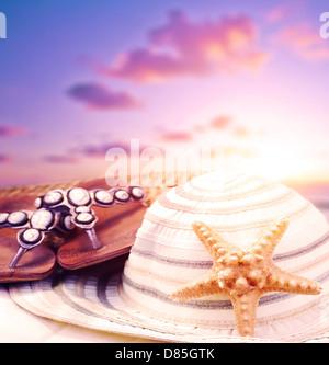 Encore gros plan de vie accessoires de plage violet sur fond coucher de soleil, tongs et womens hat décoré avec Banque D'Images