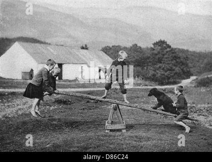 Les enfants et un chien jouent sur une balançoire Banque D'Images