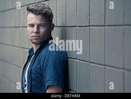Homme debout contre le mur de bloc