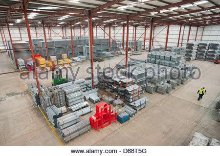 Marche des travailleurs à travers l'entrepôt avec des tubes d'acier et des barrières de sécurité terminé Banque D'Images