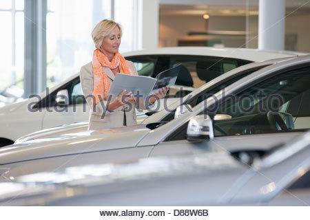 Client à la brochure à côté de car in car dealership showroom Banque D'Images