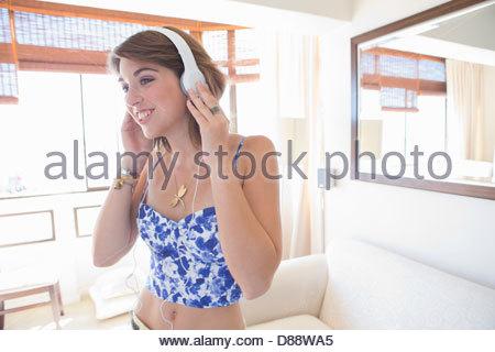 Jeune femme portant des écouteurs dans la salle de séjour Banque D'Images