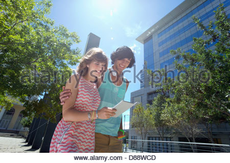 Smiling young couple using digital tablet in city Banque D'Images