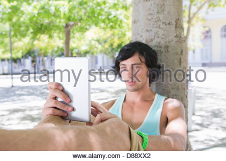 Young man using digital tablet against tree in park Banque D'Images