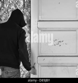 Silhouette encapuchonnée sortant par la porte d'une maison abandonnée. Banque D'Images