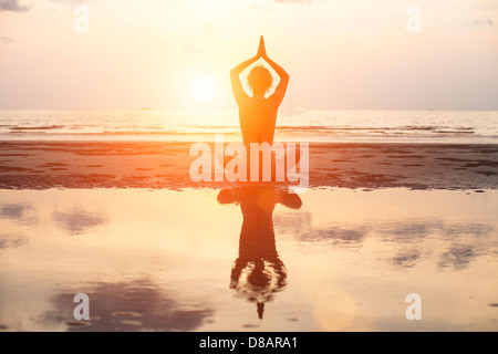 Yoga woman sitting in lotus pose sur la plage pendant le coucher du soleil, avec la réflexion dans l'eau (en couleurs)