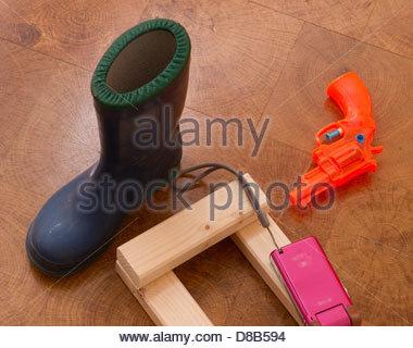 Enfants, jouets, Wellington Boot, pistolet à eau sur plancher en bois Banque D'Images