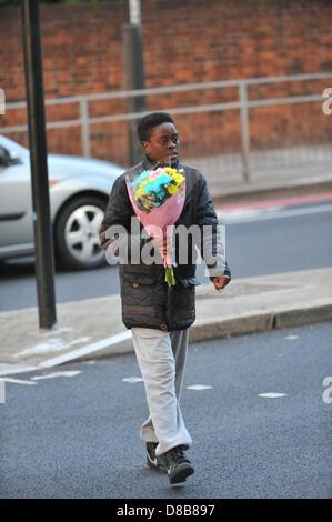 Woolwich, Londres, Royaume-Uni. 23 mai 2013. Un jeune garçon porte les fleurs à laisser sur les grilles près du lieu du meurtre. Les fleurs sont laissés par les bienfaiteurs le long des rampes près de l'endroit où le batteur Lee Rigby du 2e Bataillon du Régiment royal de fusiliers a été tué hier à l'extérieur des casernes de Woolwich. Crédit: Matthieu Chattle/Alamy Live News